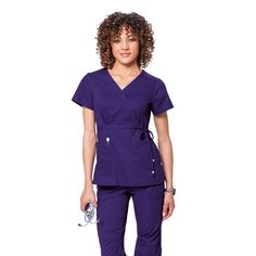 Koi Katelyn Wrap Style Tunic. £27.50 on happythreads. The Koi Katelyn top is designed with stunning detail. This scrub top is wrap style top with adjustable ties. The scrub top also gathers at the back giving you a more defined shape. There are two front pockets and side slits which allows ease of movement.  #nursescrubs #dentistuniform #nurses #dentists #purplescrubs
