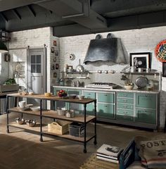 """The Loft kitchen (above) has a more industrial feel. Adding to its traditional flair, we love the '50s-era pastel teal color complementing the steel-patchwork range hood and handles. Paired with stainless steel appliances, the look is """"old-fashioned for the future."""""""