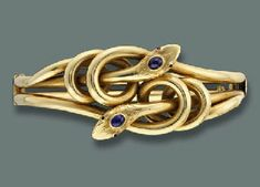 An Antique Snake Bangle And A Bracelet, The two entwined snakes with ruby eyes and cabochon sapphire crowns to the hinged bangle, circa 1890, 7.5 cm. wide, with French import marks; and a twin-line mesh bracelet with knot centre (not illustrated), 17.5 cm. long. The snake bangle was given by King Umberto II to his daugther Princess Maria Gabriella of Savoy (Christie's)
