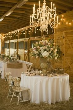 Barnyard chandelier love wedding lights decor flowers country barn rustic table centerpiece