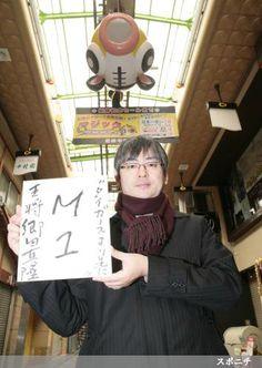 「日本一早い優勝マジック」と書かれたアーケードで「タイガースより先に」を書いた色紙を笑顔で持つ郷田真隆王将 (Photo By スポニチ)