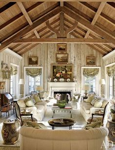 A Florida living room's pecky-cypress paneling was lightened by decorative painter Bob Christian, whose work can also be seen on the tile fireplace surround. The landscape paintings are 19th-century English, the roll-arm sofas are by O. Henry House, and the Louis XV-style armchairs by Edward Ferrell + Lewis Mittman, in the foreground, are upholstered in a Brunschwig & Fils floral; Chinese rice barrels serve as occasional tables. Pin it.