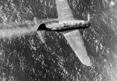 With its gunner visible in the back cockpit, this Japanese dive bomber, smoke streaming from the cowling, is headed for destruction in the water below after being shot down near Truk, Japanese stronghold in the Carolines, by a Navy PB4Y on July 2, 1944. Lieutenant Commander William Janeshek, pilot of the American plane, said the gunner acted as though he was about to bail out and then suddenly sat down and was still in the plane when it hit the water and exploded.