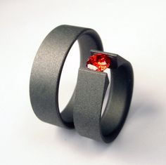 Matte Titanium Tension-set ring and Men's band Set $449.00   This is just a striking set of rings. A men's wedding band and a tension setting engagement ring. Ultra modern design, clean and conflict free. The dark titanium matte finished band with the red stone is a brilliant combo. Dark gray and red have always been a great color combo and very cool to see it in a ring. If you like this ring but not the stone Zoe And Doyle has a number of stones you can request.  from Zoe And Doyle