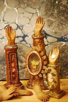 Reliquary Santon Hand Shrines  by Colleen Baptista via Flickr. The hands are made of carved wood. After making the basic reliquary box ( no soldering just copper tape) the base is shaped from a piece of poster board and then covered in Apoxie clay. While the clay is still workable you can add beads or indent with other objects. Then you add the reliquary.