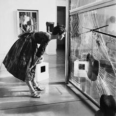 """Modèle devant la partie basse du """"Grand verre"""" (1915-1923), de Marcel Duchamp, exposé au Philadelphia Museum of Art, en 1954"""
