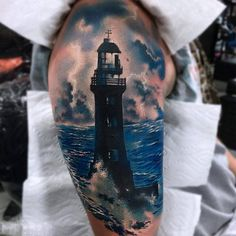 realistic lighthouse tattoo on shoulder
