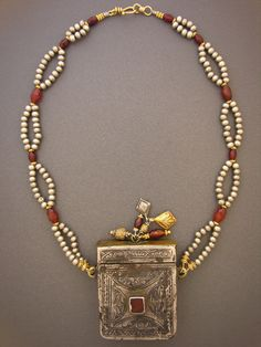 by Anna Holland | Anna found this exquisite antique box pendant in her travels through Morocco. And it still opens on top. Great niello work and carnelian on front, and Anna added a tassel on top. A mixture of silver beads, faceted carnelians, gold-filled accents and other antique beads round out the piece. The gold-filled hook and eye clasp was handmade in Sri Lanka. | 575$
