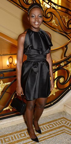 As queen of monochromaticism, Lupita Nyong'o stepped out for the Sindika Dokolo Art Foundation in a head-to-toe black, accessorizing her ruffled Fitriani LBD with a mini ladylike bag and black pumps. The crown jewel of her look? Her pretty delicate headband.