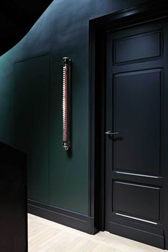 This black and dark green interior paint palette adds a modern touch to this hallway. Studio Ko Paris This black and dark green interior paint palette adds a modern touch to this hallway. Studio Ko Paris Click The Link For See Dark Green Walls, Dark Walls, Dark Interiors, Colorful Interiors, Interior Paint Palettes, Paris Loft, Dere, Basement Bedrooms, Bedroom Doors