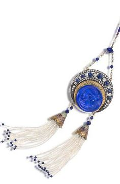 An enamel, lapis and gem-set pendant necklace centering a lapis cameo cuvette within an enamel surround highlighted by cushion-shaped sapphires and old mine-cut diamonds, with a double seed pearl fringe, suspended from an enamel baton-link chain, with rose-cut diamond and lapis bead accents; mounted in gold and silver.
