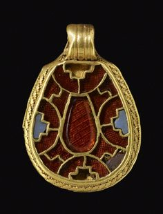 Gold tear-shaped pendant set with garnets and blue glass and with filigree rim. AN1124722001  © The Trustees of the British Museum  Department: Prehistory and Europe