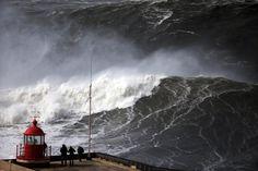IlPost - Nazaré, Portogallo - Alcune persone osservano le onde gigantesche del mare infrangersi contro il faro, nel villaggio di Nazaré, Portogallo.  (AP Photo/Francisco Seco)