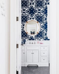 The patterned wallpaper is the focal point. The visual hierarchy leads to the mirror with its round shape and gold touches. Then the eye drops further down to the white cabinets that match the mirror but are a different shape.