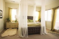 added height and a breezy and cozy vibe to their bedroom, thanks to sheer curtains from Ikea that she hung from the ceiling for a makeshift canopy affect.