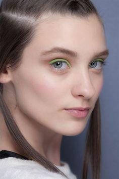 Pele: Blush rosa e iluminador.  Olhos: Delineado fluo (rosa ou verde ou azul) e sombra marrom claro.  Boca: Batom nude.
