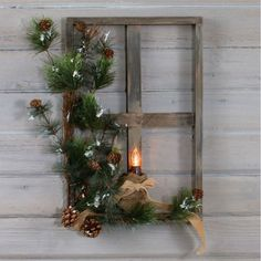 Woodsy pine boughs, pine cones and a glowing candle in front of a vintage look window frame. A burlap cover and rustic bow completes this seasonal favorite. Add your own Christmas touches or leave up