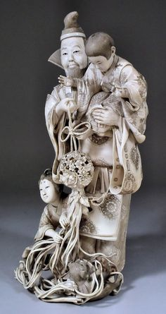 A fine Japanese (Tokyo School) carved ivory okimono in the form of a standing bearded man holding a young child on his left shoulder and carrying a flower ball in his right hand, and with female attendant, dog and hobby horse below, 13.5ins (343mm) high, apparently unsigned ( Meiji period)