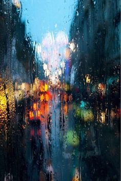 Vivid rain-streaked city window