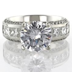 A Judith Conway engagement ring with round center, channel set princess cuts and micro pave'.