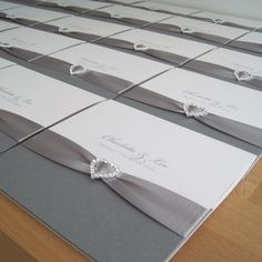 Albany Pocketfold Wedding Invitations in white and grey and finished with silver ribbon and a crystal heart.