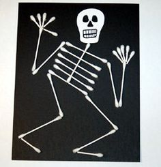 Prepare your Q-tip bones beforehand.  Cut off the ends for toes and fingers.   Pipe glue down the middle of the black paper. Start with the spine and glue on your pieces one by one to build your skeleton.   Cut a simple skeleton head from white paper. Add black lines for teeth and eyes.