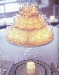 Cute and cheap! Lots of little candles and a multi-tiered cake plate for each table. Arrange the candles on each cake plate to create a stunning illusion..so beautiful for a wedding....use the wedding theme color...it would also make a beautiful christmas centerpiece with green or red candles...I love this idea!!!!!