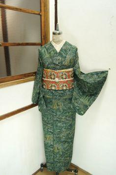 緋色地に深みのある緑と芥子が美しく調和した彩りも華やかに、正倉院狩猟文様が染め出された京袋帯です。