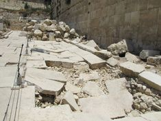 Fallen stones from the Temple and Temple Mount lay in a heap at the base of the Western Wall towards the back right of this photo.  The crushed pavement is the result of the impact from these stones in 70 AD.
