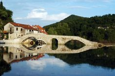 Four-arched bridge of Rijeka Crnojevica reflected in Lake Skadar.    Read more: http://www.lonelyplanet.com/montenegro/travel-tips-and-articles/76648?affil=twit#photo-22778-3#ixzz1nJYsrz1n