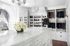 Gorgeous Closet Features Two Chandeliers Illuminating A Long Closet Island  Fitted With Drawers For Accessories Topped With Marble Countertop.