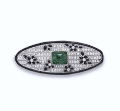 AN ART DECO EMERALD, DIAMOND AND ONYX BROOCH, BY MARCHAK