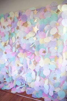 This gorgeous pastel paper garland backdrop would be a stunning accent for birthdays, weddings, or any other special occasion. This airy garland captures light beautifully to create a whimsical backdrop for any event. The display features a mixture of pinks, purples, yellows, and