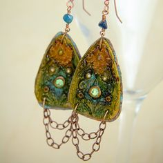 Polymer clay drop earrings with 5 small Swarovski crystals and 1 large Swarovski crystal in the center. After removing the clay from the mold the artist hand pressed a design into it's surface and cured it twice for added durability. It is hand stained and sealed to protect the surface colors from handling.