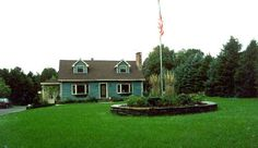 Goshen stone wall creating a raised planting bed with flag pole set in the front lawn.