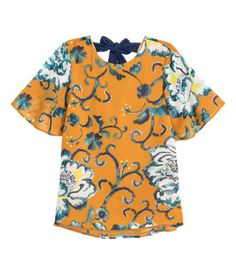Short-sleeved blouse in chiffon with a printed pattern. Low-cut V-neck at back with tie at back of neck. Lined.