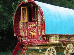 Bow Top Vardo - Turquoise canvas as a roof and traditional ornate scrollwork/painting with horse depicted on the door.