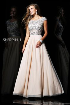 This prom gown has a beaded, cap sleeve top and elegant chiffon bottom.