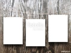 Close-up of three hanged paper sheet frames with pegs on wooden background