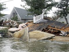 Water flows past debris from a destroyed home yesterday in Mantoloking, New Jersey. Hurricane Sandy caused the ocean to cut a channel through to the bay, shown flowing here, which effectively cut the borough in two. Most of the multimillion-dollar homes along this old-money stretch of the Jersey shore were seriously damaged by pounding surf, wild wind and, in some cases, fire from ruptured gas lines. Numerous homes were destroyed, and some were obliterated, leaving behind just empty sand or…