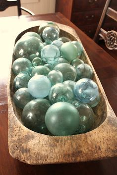 Tabletop dining room decor with glass floats in wood bowl.