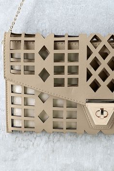 "Great things are taking shape, and the final product is the Geo du Jour Cutout Taupe Clutch! Taupe vegan leather is covered in geometric cutouts for a style that's totally chic and unique. Front flap boasts a shiny gold twist-lock closure that opens to reveal taupe lining in one main compartment, with a small zipper pocket at back. Carry as a clutch or clip on the 46"" long gold chain strap."