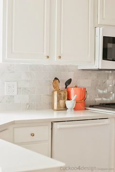 Carrera marble backsplash, white quartz counter, champagne hardware.