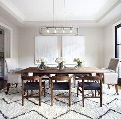 mesa del comedor con alfombra grande, dos cuadros y sillas diferentes para dar color, en marrón oscuro y azul marino y dos cuadros simétricos (en el techo poner luz indirecta) y flores encima de la mesa
