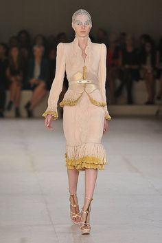 Alexander McQueen Spring 2012.  Great shape, love the trim and the braid/scallop high neckline.  Never liked the McQueen face covering tendency, but can ignore it for the rest of the outfit.