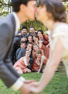 Capture a kiss! Everyone loves a good picture of the bride and groom sharing a kiss. Add a fun twist to a standard kissing picture by having your bridal party in the background of the photo. Wedding Photos, Wedding Party