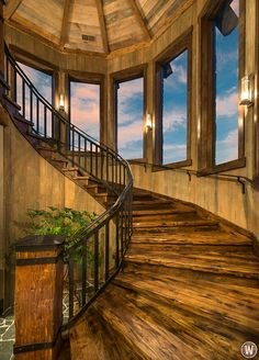 Rustic spiral staircase design with iron handrails.