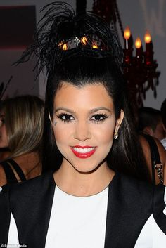 Flawless: Kourtney Kardashian wore bright red lipstick and thick fake eyelashes along with an unusual headpiece as she smiled for the camera