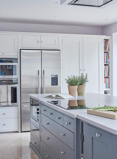 A ceiling mount vent hood stands over a blue kitchen island fitted a microwave and an induction cooktop.
