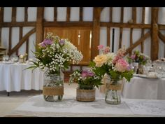 Jam jars for rustic-romantic wedding in a barn venue. Jam jars decorated with and # hessian. Made by Brigitte Flowers Hessian, Jars, Flower Arrangements, Bouquet, Romantic, Rustic, Table Decorations, Flowers, Wedding